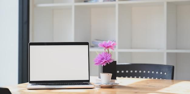 Öffnen sie laptop-computer des leeren bildschirms im bequemen arbeitsplatz mit rosa blume