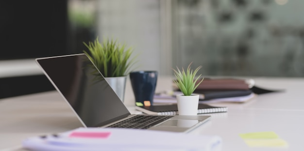 Öffnen sie laptop mit büroartikel und dokumenten auf weißer tabelle in der modernen büroart