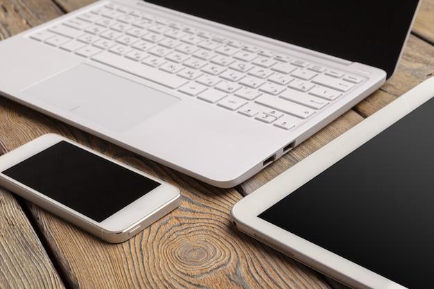 Öffnen sie laptop mit digitaler tablette und weißem smartphone