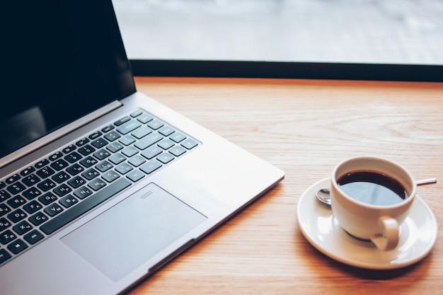 Öffnen sie laptop und einen tasse kaffee auf dem tisch im café, freiberuflich tätiges konzept