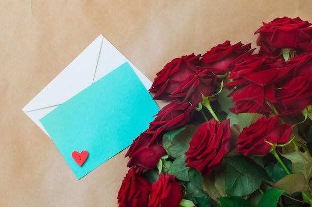 Öffnen sie leere blaue postkarte mit holzherz auf dem postumschlag nahe rosenstrauß