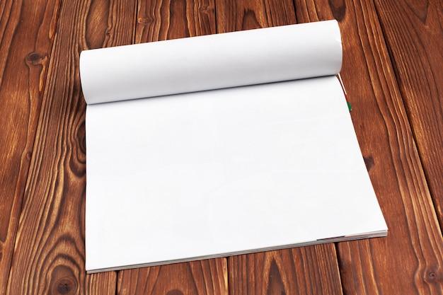 Öffnen sie leere journalseiten für ihren entwurfskopierraum auf hölzernem hintergrund