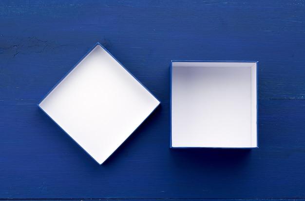 Öffnen sie leere quadratische pappschachtel für geschenke auf einem blauen hölzernen hintergrund