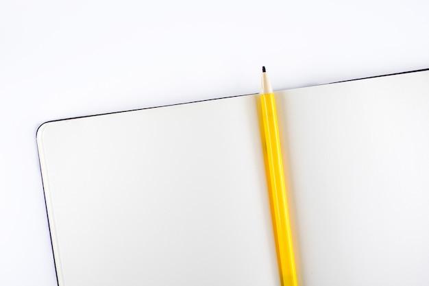 Öffnen sie leeres notizbuch mit gelbem bleistift auf weißem hintergrund, schablonenspott oben für das addieren ihres inhalts