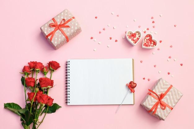 Öffnen sie leeres notizbuch mit geschenkbox, blumen und herzen auf einem rosa hintergrund
