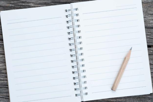 Öffnen sie leeres notizbuch und bleistift auf hölzernem hintergrund.