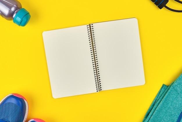 Öffnen sie leeres notizbuch und tragen sie die kleidung der frauen für sport zur schau