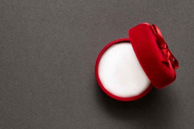 Öffnen sie leeres rotes schmuckkästchen auf einem schwarzen hintergrund. ansicht von oben. kopieren sie platz