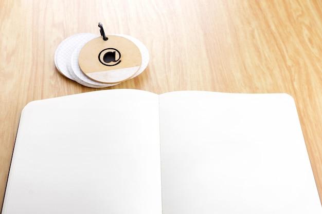 Öffnen sie notizbuch auf holztisch mit notizblock, schablonenspott oben für das addieren ihres inhalts