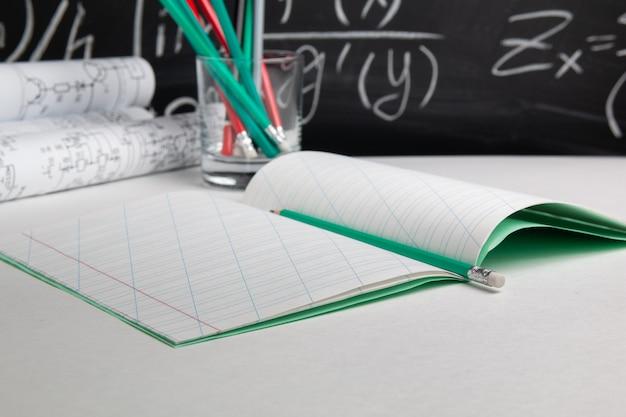 Öffnen sie notizbuch mit bleistift und zeichnungen auf tafelhintergrund. bildungskonzept.