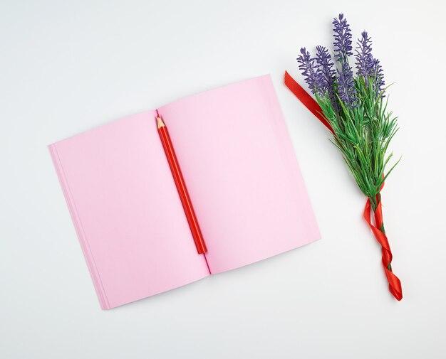 Öffnen sie notizbuch mit leeren rosa seiten, hölzernen roten bleistift