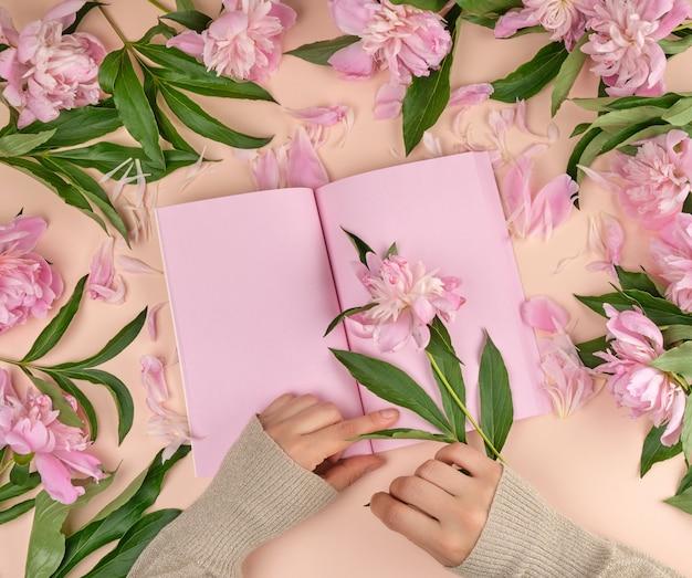 Öffnen sie notizbuch mit leeren rosa seiten und zwei weiblichen händen
