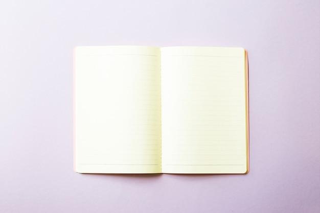 öffnen sie notizbuch mit sauberen weißen blättern auf einem purpurroten hintergrund
