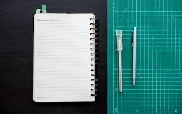 Öffnen sie notizbuch mit schneidebrettsbriefpapier auf dunkelgrauer tabelle