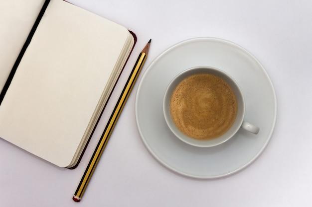 Öffnen sie notizbuch mit stift und kaffeetasse auf weißem hintergrund. arbeitskonzept. ansicht von oben. flach liegen. platz kopieren.