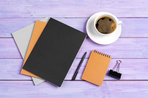 Öffnen sie notizbuch mit tasse kaffee auf hölzernem schreibtisch