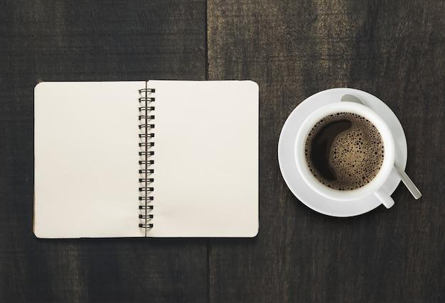 Öffnen sie notizbuch mit tasse kaffee auf schwarzem hölzernem schreibtisch.