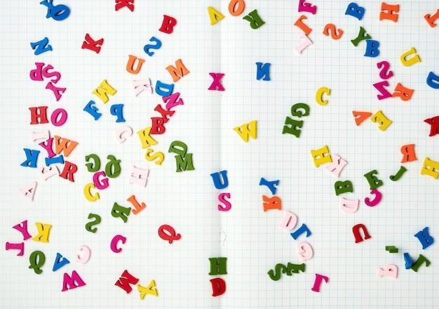 Öffnen sie notizbuch mit weißen blättern in einem kasten und kleinen mehrfarbigen hölzernen buchstaben