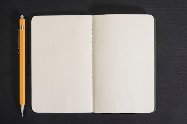 Öffnen sie notizbuch und bleistift auf schwarzem hintergrund