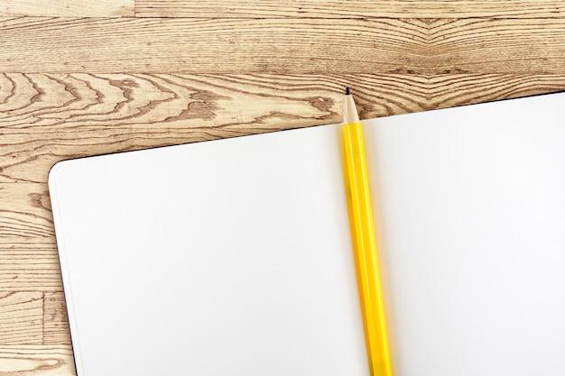 Öffnen sie notizbuch und gelben bleistift auf holztisch, draufsicht, schablonenspott oben für das addieren ihres inhalts