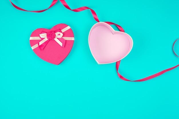 Öffnen sie rosa herzförmige geschenkbox mit einem bogen