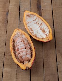 Öffnen sie roten kakao, der samen über holztisch zeigt.