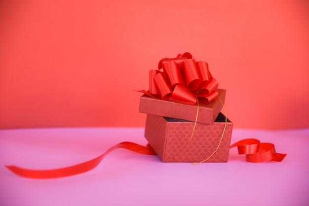 Öffnen sie roten kopienraum der geschenkbox auf rosa / rotem präsentkarton mit rotem bandbogen für geschenk