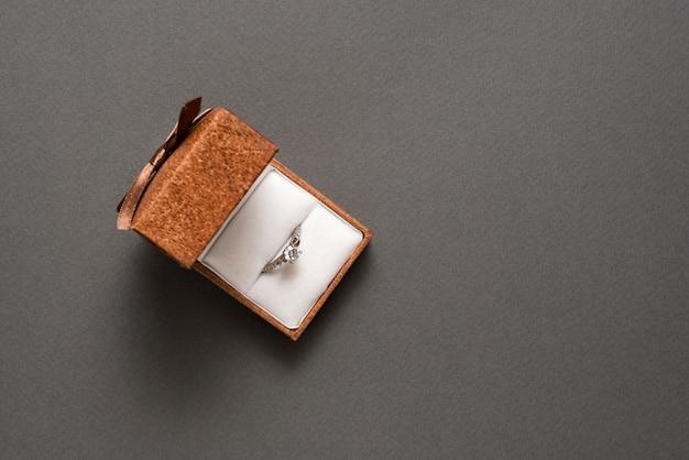 Öffnen sie schmuckschatulle mit ring auf einem schwarzen hintergrund. ansicht von oben. kopieren sie platz