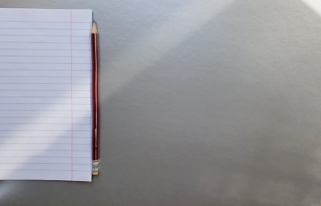 Öffnen sie schulnotizbuch mit stift auf einem grauen schreibtisch mit sonnenstrahlen aus dem fenster. ein leeres, weißes notizbuch zum schreiben. bildungskonzept. platz kopieren. von oben betrachten. flach liegen.