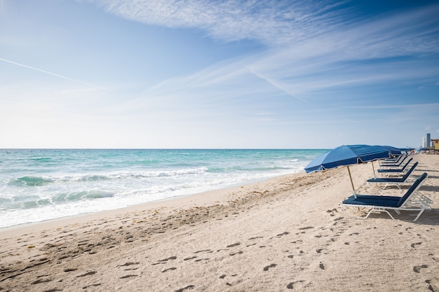 Öffnen sie sonnenschirme an einem leeren sandstrand am meer vor blauem himmelshintergrund