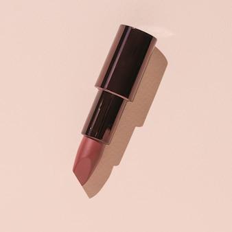 Öffnen sie stilvollen lippenstift auf einem beigen hintergrund. flach liegen.