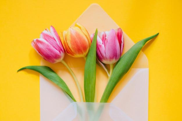 Öffnen sie transparenten mattumschlag mit mehrfarbigen tulpen auf gelbem hintergrund