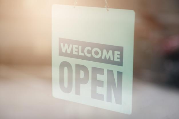 Öffnen sie und begrüßen sie zeichen weit durch das glas des fensters, um kunden wissen zu lassen