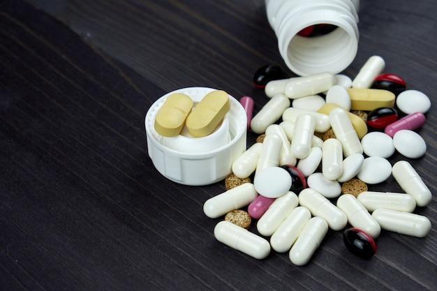 Öffnen sie verordnungsflaschen und die weißen und gelben tabletten, pillen, vitamine, medizin, pilule und drogen, die auf dunkle tabelle zerstreut werden. treanment pillen und medizin.