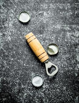 Öffner und bierdeckel. auf einem dunklen rustikalen tisch