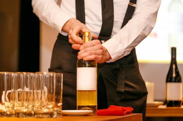 Öffnungsprozess einer weinflasche mit korkenzieher durch kellner wait