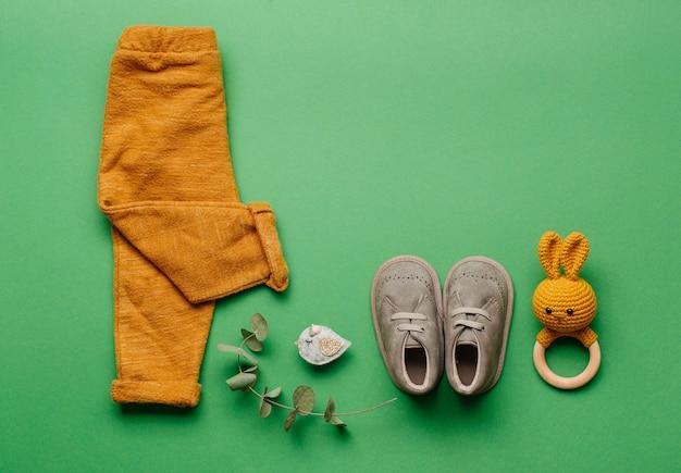 Öko babykleidung und accessoires konzept. baby holzspielzeug beißring kaninchen, hosen und schuhe auf grünem hintergrund mit leerzeichen für text. draufsicht, flach liegen.