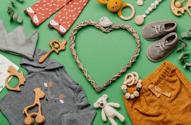 Öko babykleidung und accessoires konzept. holzherz mit rahmen von babyspielzeug, kleidung und schuhen auf grüner oberfläche mit leerzeichen für text. draufsicht, flach liegen.