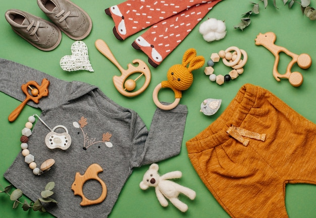 Öko babykleidung und accessoires konzept. holzspielzeug, kleidung und schuhe auf grüner oberfläche mit leerzeichen für text. draufsicht, flach liegen.