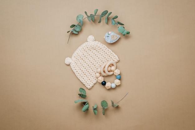 Öko-babyzubehörkonzept. hölzerner beißring und babymütze auf beigem hintergrund mit leerzeichen für text. draufsicht, flach liegen.