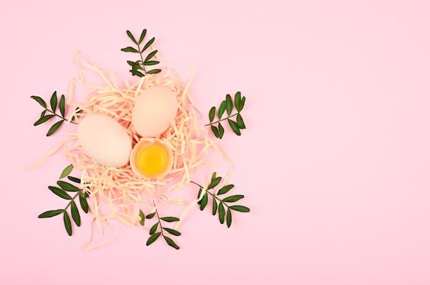 Öko-eier auf einem rosa hintergrund. ein tablett mit eiern auf einem weißen und rosa hintergrund. öko-tablett mit hoden. minimalistischer trend, draufsicht. eierablage. osterkonzept.