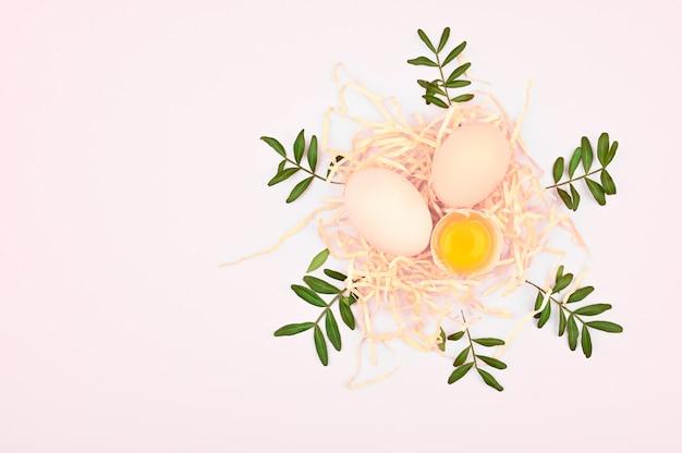 Öko-eier auf einem weißen hintergrund. ein tablett mit eiern auf einem weißen und rosa hintergrund. öko-tablett mit hoden. minimalistischer trend, draufsicht. eierablage. osterkonzept.