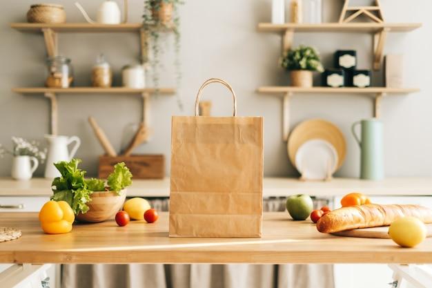 Öko-einkaufspapiertüte mit frischem gemüse und baguette auf dem tisch in der küche