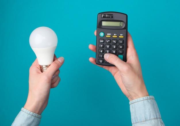 Öko, energie sparen konzept. weibliche hände halten taschenrechner und glühbirne auf blau.