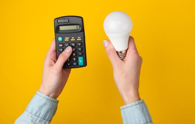 Öko, energie sparen konzept. weibliche hände halten taschenrechner und glühbirne auf gelb.