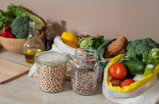 Öko-freundliche baumwolltaschen mit lebensmitteln, ölflasche und gläsern mit kichererbsen und quinoa. kein verlust. veganes naturkost. lokale bio-lebensmittel. nachhaltiger lebensstil