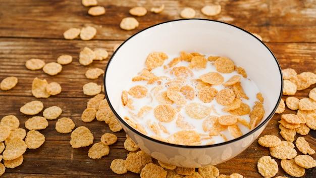 Öko gesunde lebensmitteloberfläche. cornflakes mit milch. milchflocken in einer weißen schüssel. gesundes essen und frisches frühstück