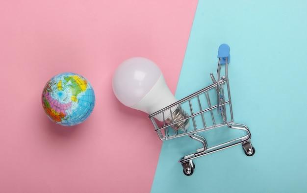 Öko-konzept. einkaufswagen mit led-glühbirne und globus auf einem blau-rosa pastellhintergrund. draufsicht.