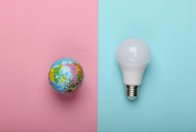 Öko-konzept. led-glühbirne und globus auf einem blau-rosa pastellhintergrund. draufsicht.