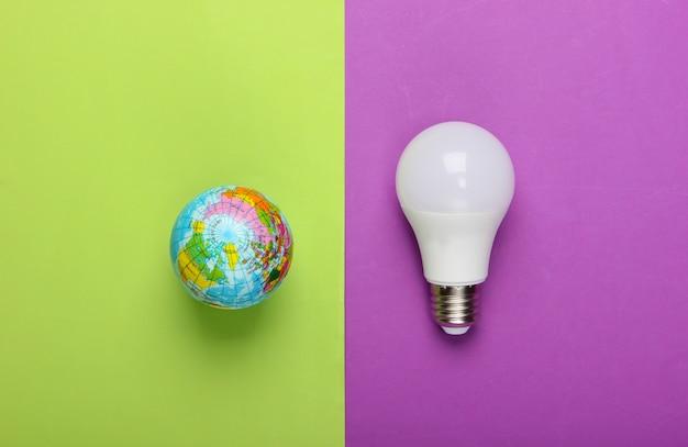 Öko-konzept. led-glühbirne und globus auf grünem lila hintergrund. draufsicht.